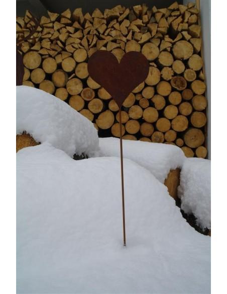 Herz Gartenstecker als Winterdeko im Schnee vor einem Holzstapel
